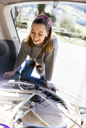 Young woman putting bicycle into car