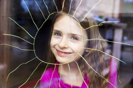 Portrait of smiling girl looking through windowpane with painted sun LANG_EVOIMAGES