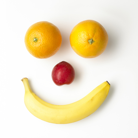 Smiley face built of fruits  on white ground