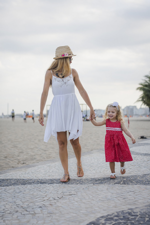 Brasil, Rio de Janeiro, mother and daughter walking on Copacabana beach