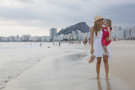 Brasil, Rio de Janeiro, mother carrying and kissing daughter on Copacabana beach