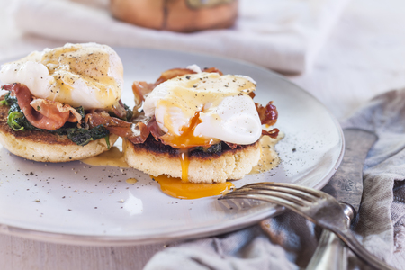 Egg Benedict with english muffins, poached eggs, ham, braised spinach, and Hollandaise LANG_EVOIMAGES
