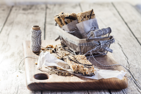 Homemade granola bars with amaranth and black chocolate on wooden board LANG_EVOIMAGES