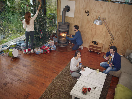 fireplace: Friends preparing for Christmas Eve in cozy living room LANG_EVOIMAGES