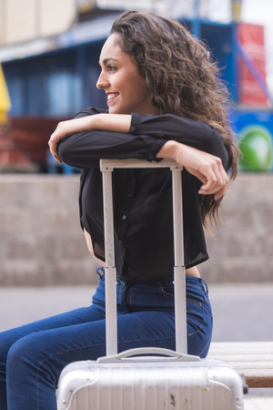 Smiling teenage girl leaning on handle of her case LANG_EVOIMAGES