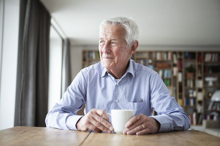 Portrait of pensive senior man sitting at table with cup of coffee looking through window LANG_EVOIMAGES