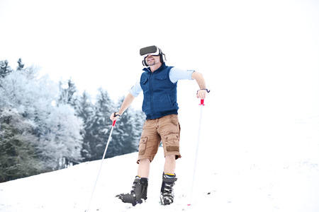 Man wearing Virtual Reality Glasses in winter landscape LANG_EVOIMAGES