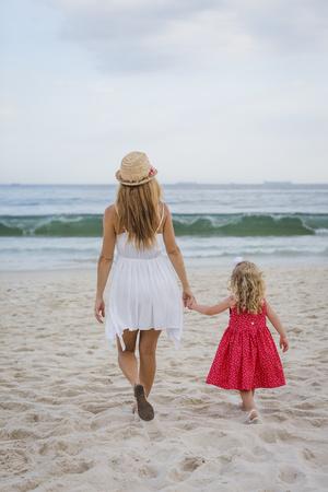 sandalias: Brasil, Río de Janeiro, madre e hija caminando en la playa de Copacabana