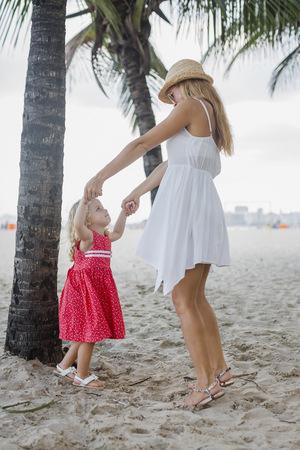 sandalias: Brasil, Río de Janeiro, madre e hija jugando en la playa de Copacabana