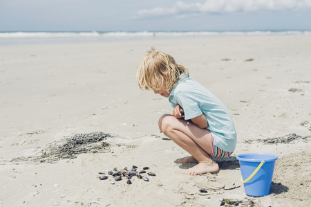 cowering: France, Brittany, Finistere, Pointe de la Torche, boy playing with seashells on the beach LANG_EVOIMAGES