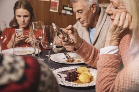 irrespeto: Miembros de la familia jugando con sus teléfonos inteligentes después de la cena de Navidad