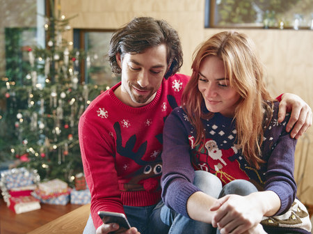 Happy couple taking selfie in front of Christmas tree LANG_EVOIMAGES