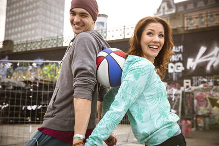 Happy young couple with basketball outdoors LANG_EVOIMAGES