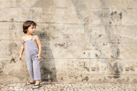 sandalias: Niño pequeño que se coloca delante de la pared de cemento en verano