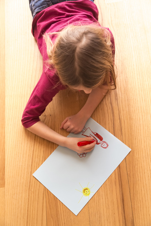 children painting: Drawing girl lying on wooden floor