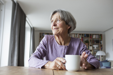 likeable: Portrait of senior woman sitting at table with cup of coffee looking through window