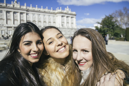 ardor: Spain, Madrid, three happy women taking a selfie in front of royal palace LANG_EVOIMAGES