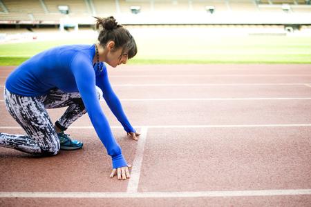 Female athlete training for race in stadium