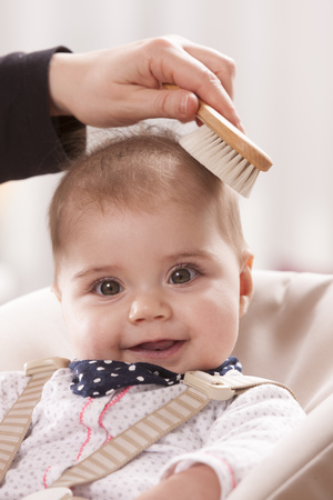 ardor: Portrait of happy baby girl brushed by her mother