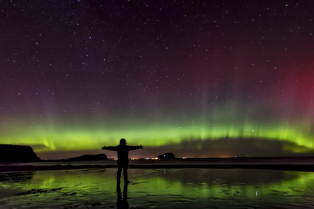 lighted: Scotland, East Lothian, silhouette of woman standing on Seacliff Beach watching Northern lights LANG_EVOIMAGES