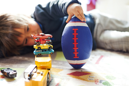 Boy lying on floor with football and stack of toy cars