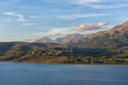 Italy, Abruzzo, Gran Sasso e Monti della Laga National Park, Lake Campotosto and town Campotosto at sunset