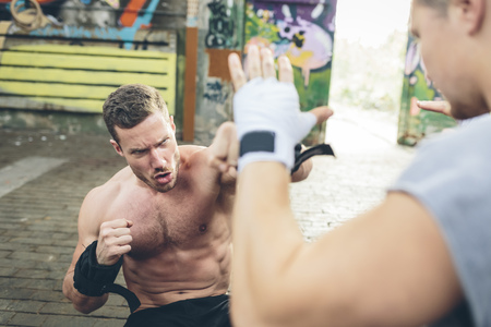 tough: Two young men having a boxing workout
