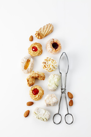 Different sorts of Italian almond cookies, pastry tong  and almonds on white background
