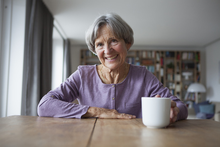 likeable: Portrait of senior woman sitting at table with cup of coffee