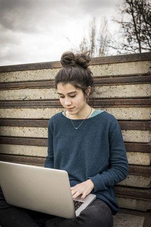 Teenage girl sitting outdoors using laptop