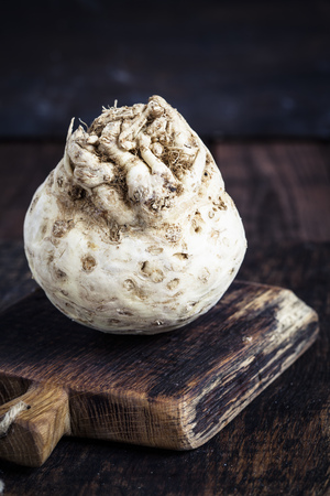 Celeriac on wooden chopping board on dark wood