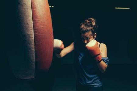 tough: Female boxer exercising at punch bag