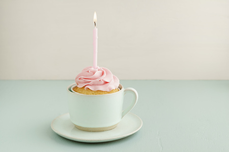 Cup cake with lighted candle in a cup