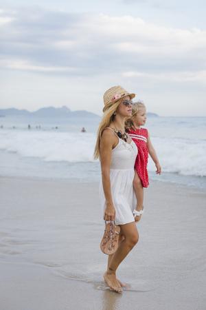 sandalias: Brasil, Río de Janeiro, madre con hija en la playa de Copacabana