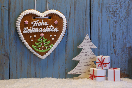 Artificial snow, Christmas decoration and gingerbread heart in front wooden wall