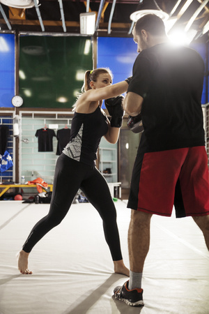 tough: Female boxer sparring with coach