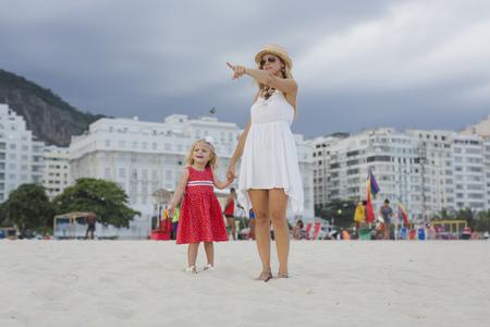 Brasil, Rio de Janeiro, mother and daughter on Copacabana beach LANG_EVOIMAGES