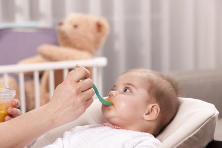 Mothers hand feeding baby girl
