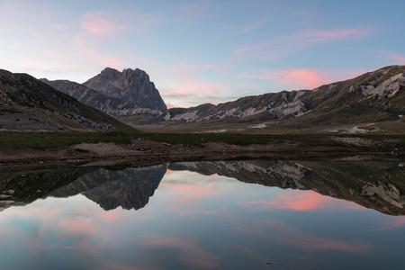 secluded: Italy, Abruzzo, Gran Sasso e Monti della Laga National Park, plateau Campo Imperatore, Corno Grande peak reflected in lake Petranzoni at sunset