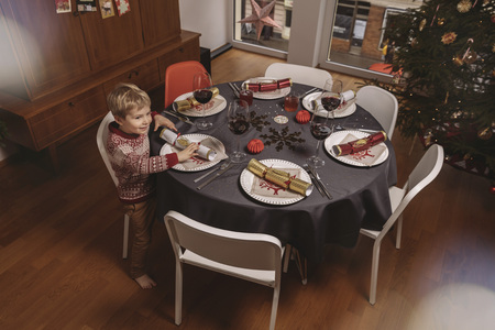 dining table and chairs: Boy at Christmas dinner table with Christmas crackers