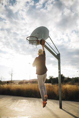 Young man playing basketball on an outdoor court LANG_EVOIMAGES