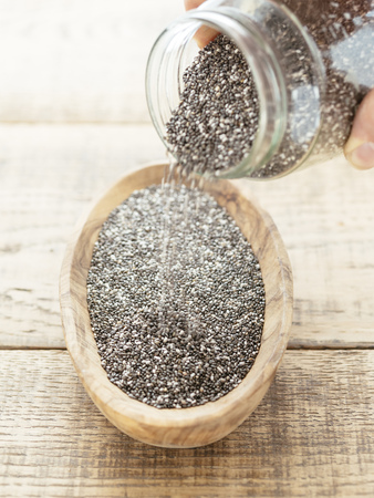 Chia seeds being poured into a wooden bowl