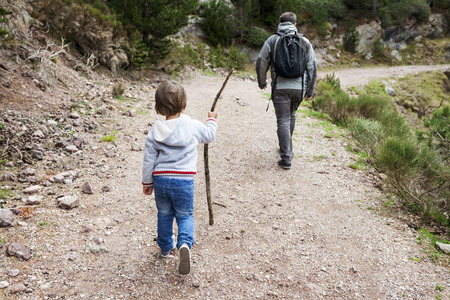Father and son hiking on rural path