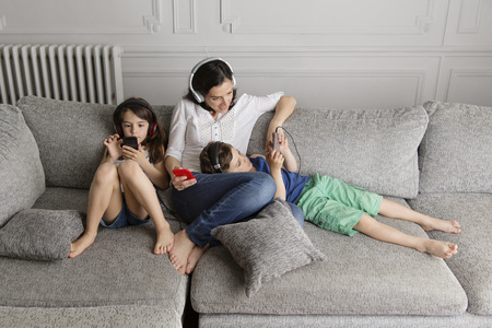 three generations: Mother and her children sitting on the couch listening music with their headphones and smartphones