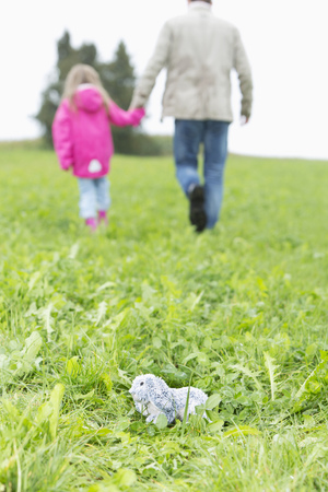 Cuddly toy lying on meadow while man going away with little girl LANG_EVOIMAGES