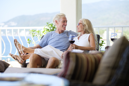 man drinking water: Happy senior couple with glass of red wine in home by the sea