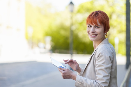 Smiling young woman outdoors with digital tablet LANG_EVOIMAGES