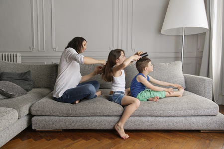 three generations: Mother and her children sitting in a row on the couch combing their hair with hairbrushes
