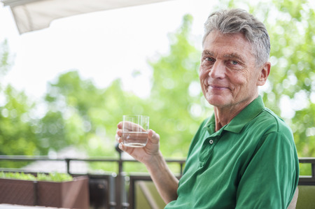 man drinking water: Portrait of smiling senior man sitting on balcony holding glass of water