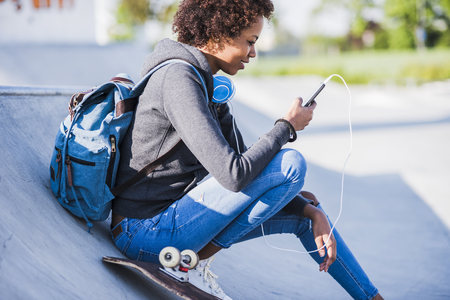 Young woman with headphones, cell phone and skateboard